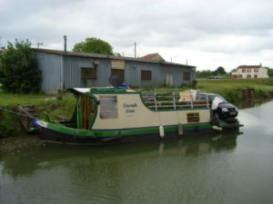 Narrow boat with car on deck